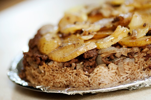 A traditional Jordanian Maqlubeh (known as Magloubeh). Thick-cut potatoes are usually added to the dish. The name is translated as 'upside down' since the dish is flipped upside-down when served.