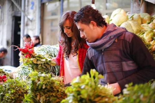 Maria picking up fresh greens from the central vegetables market